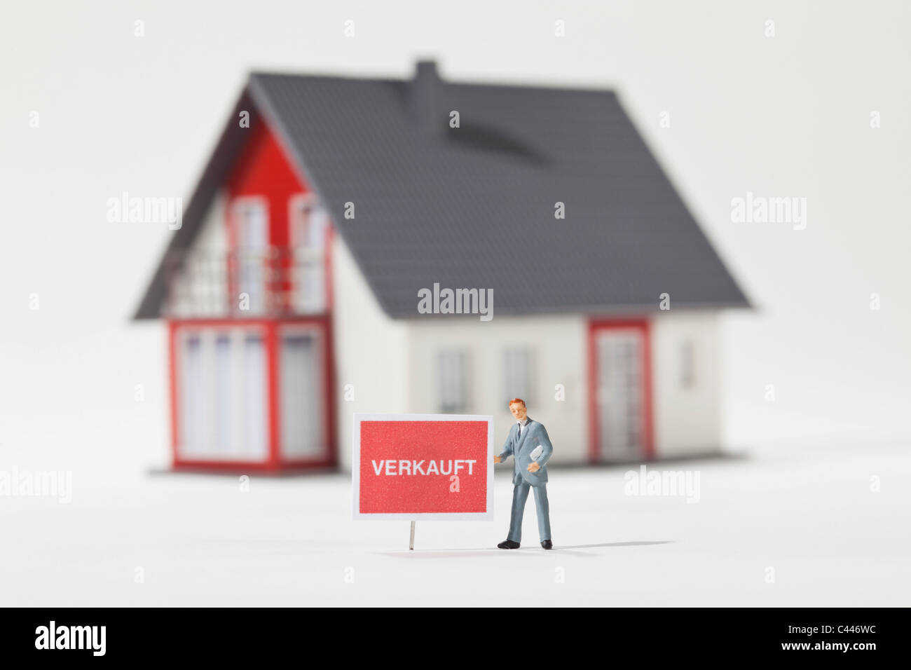 A miniature real estate agent figurine standing next to a VERKAUFT (sold in German) sign - Stock Image