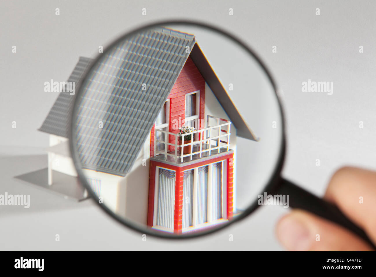 A model house viewed through a magnifying glass - Stock Image