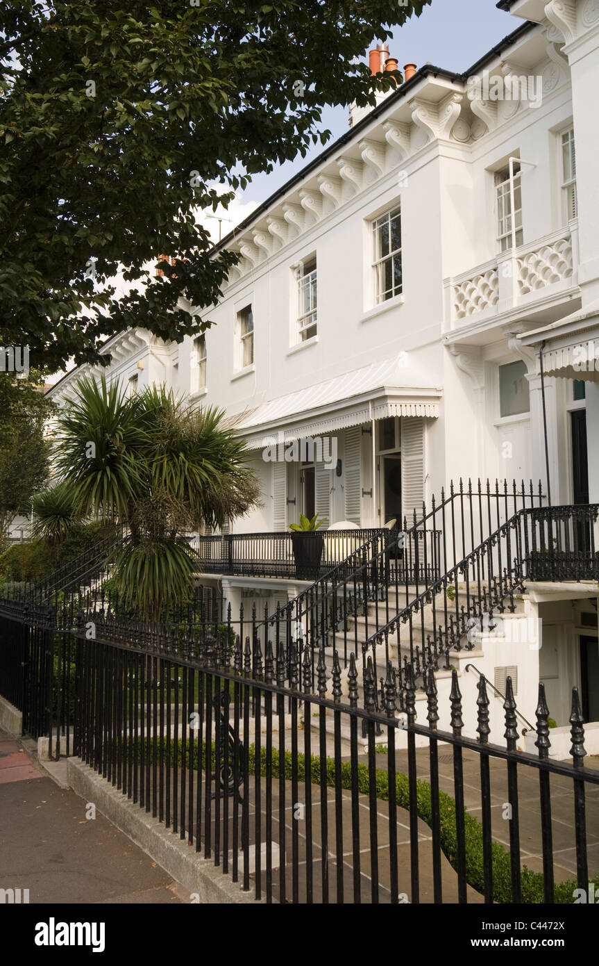 Exterior facade of Brighton Grade II listed building with railings and palm tree - Stock Image