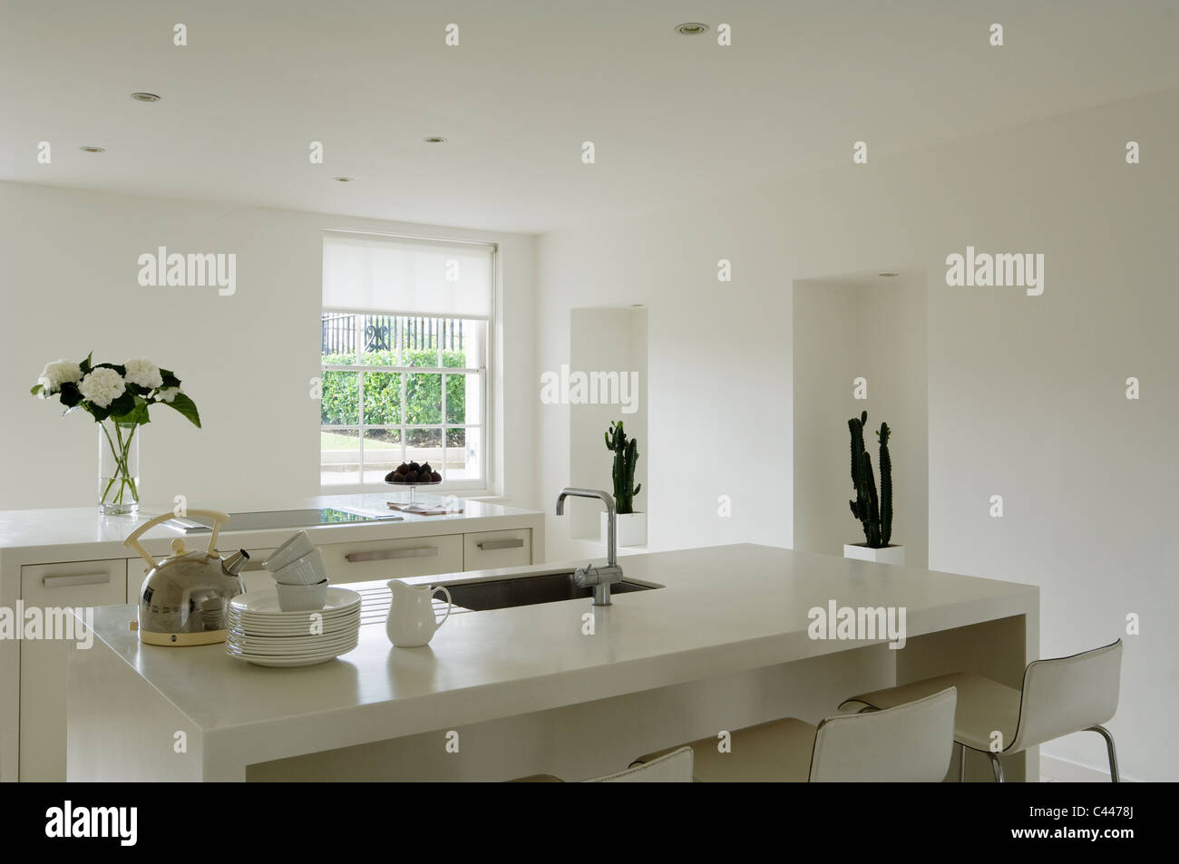 Contemporary minimal kitchen with Corian worktops and white walls - Stock Image