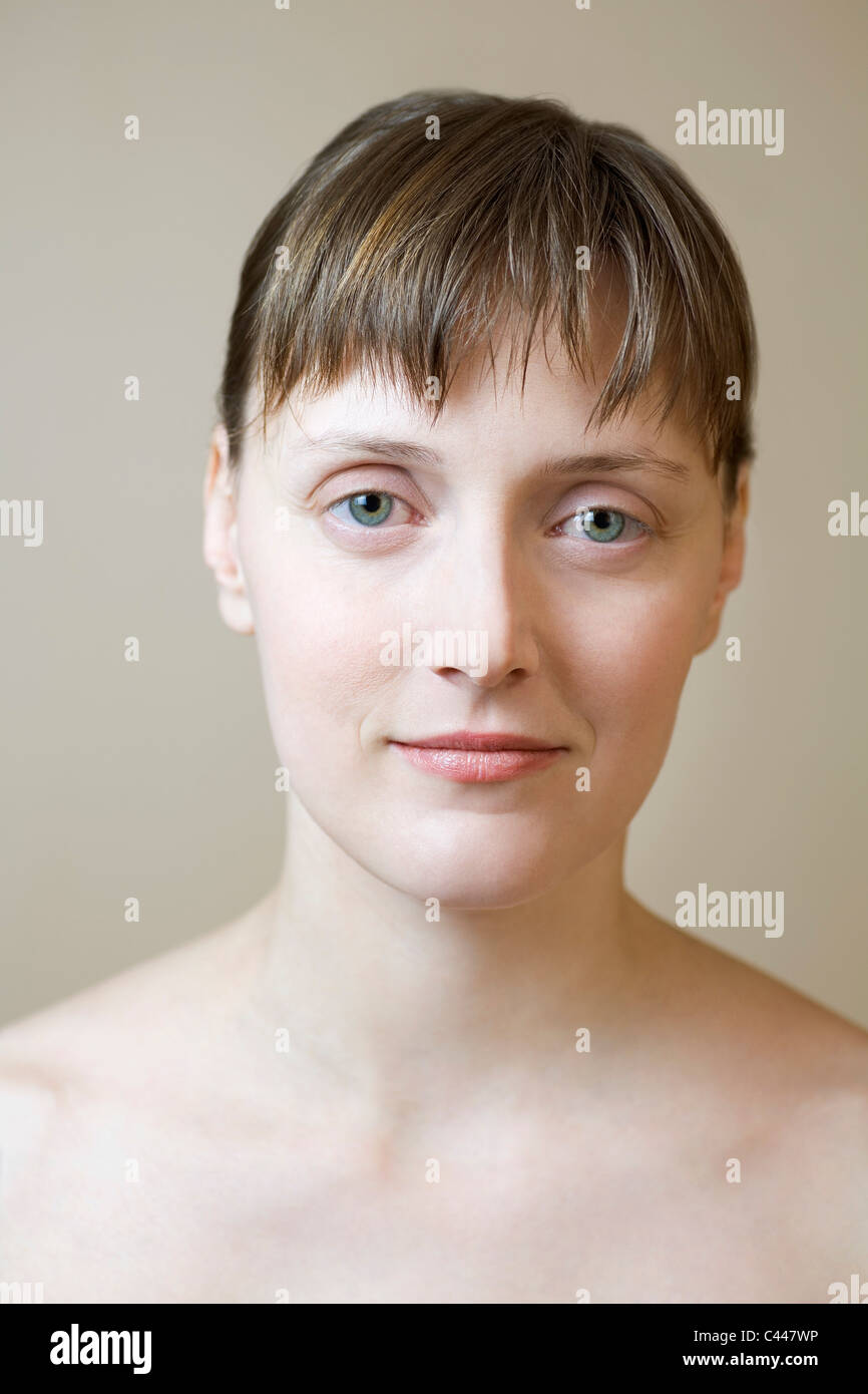 A woman with bare shoulders staring intently into the camera - Stock Image