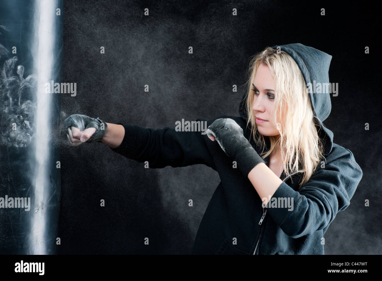 Blond boxing woman in black training with punching bag Stock Photo