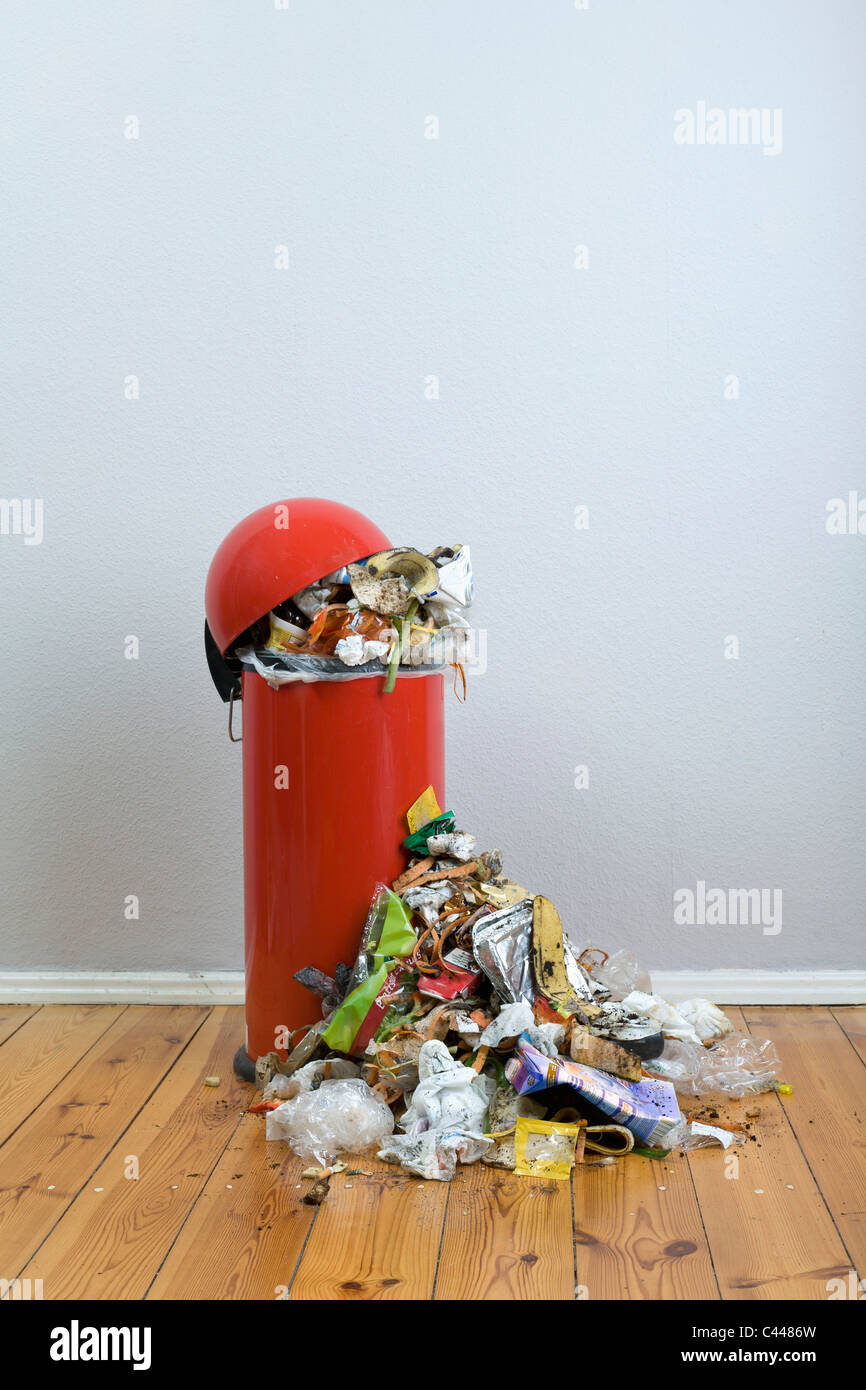 An overflowing garbage can of rotting food and recyclables - Stock Image