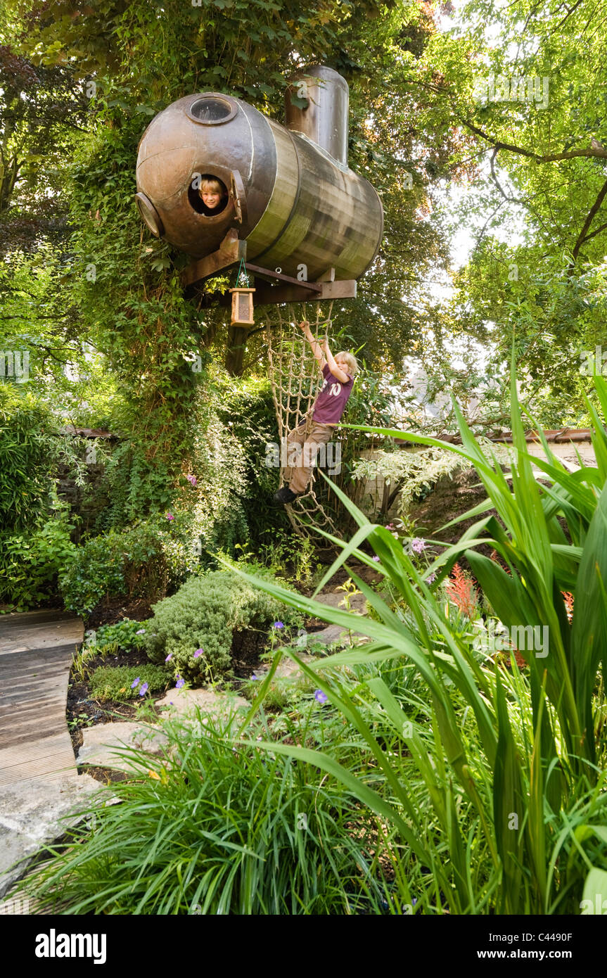 Submarine Tree House With Net In Garden With Grasses And Decking