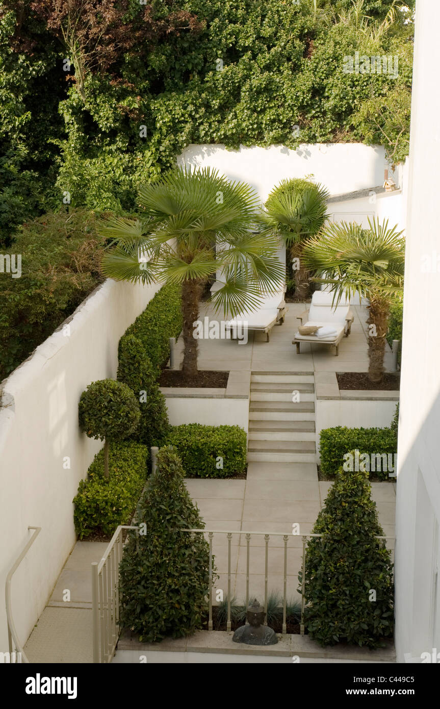 Walled garden terrace with topiary, sun loungers and palm trees. - Stock Image