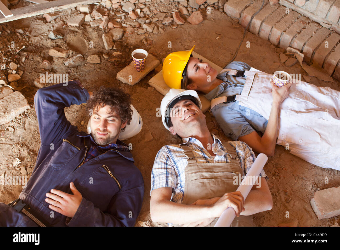 Three construction workers taking a coffee break - Stock Image
