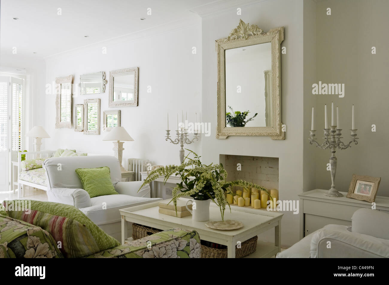 White living room with coffee table, mirror and floral patterned ...