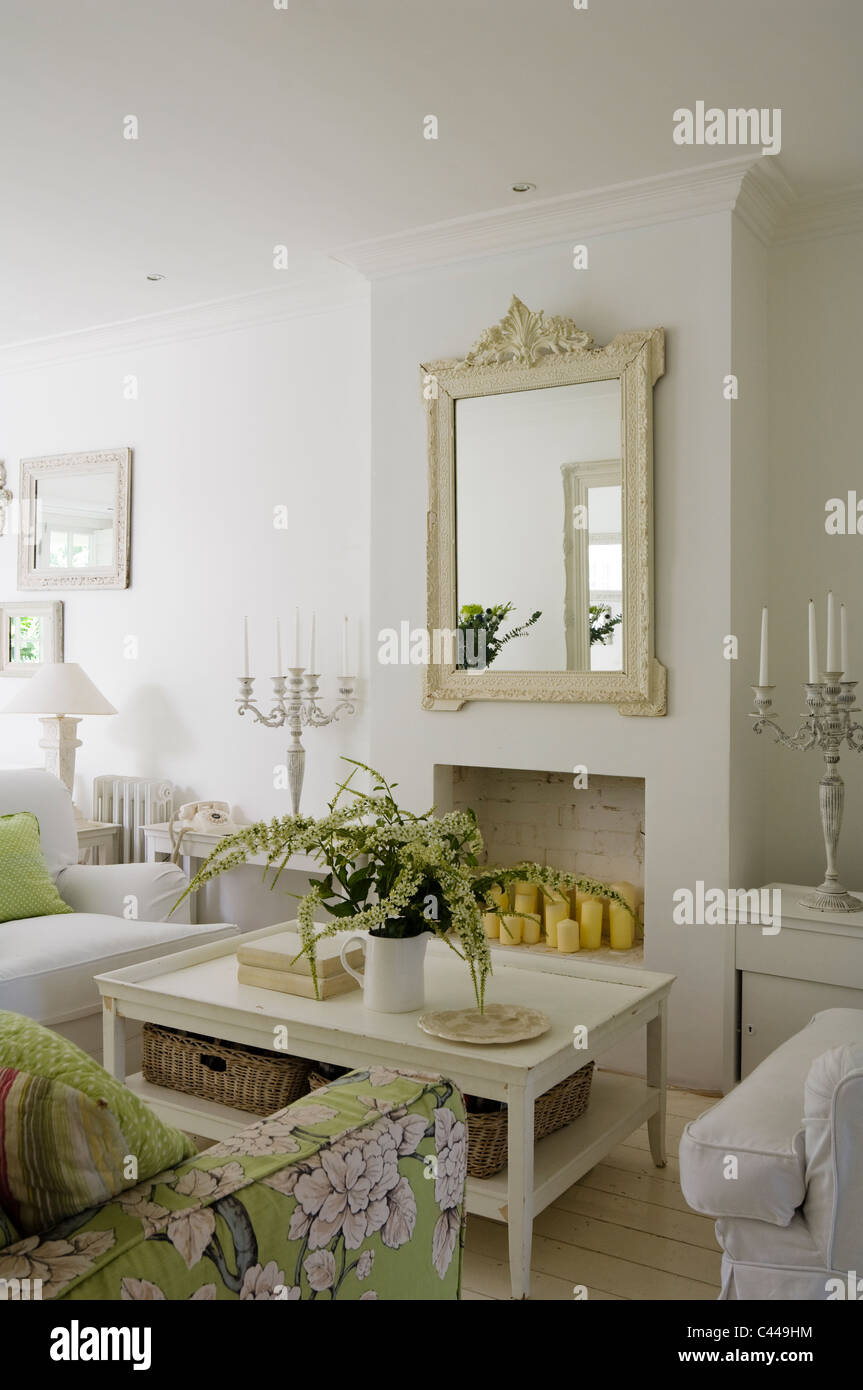 White living room with coffee table, mirror and floral patterned sofa. - Stock Image