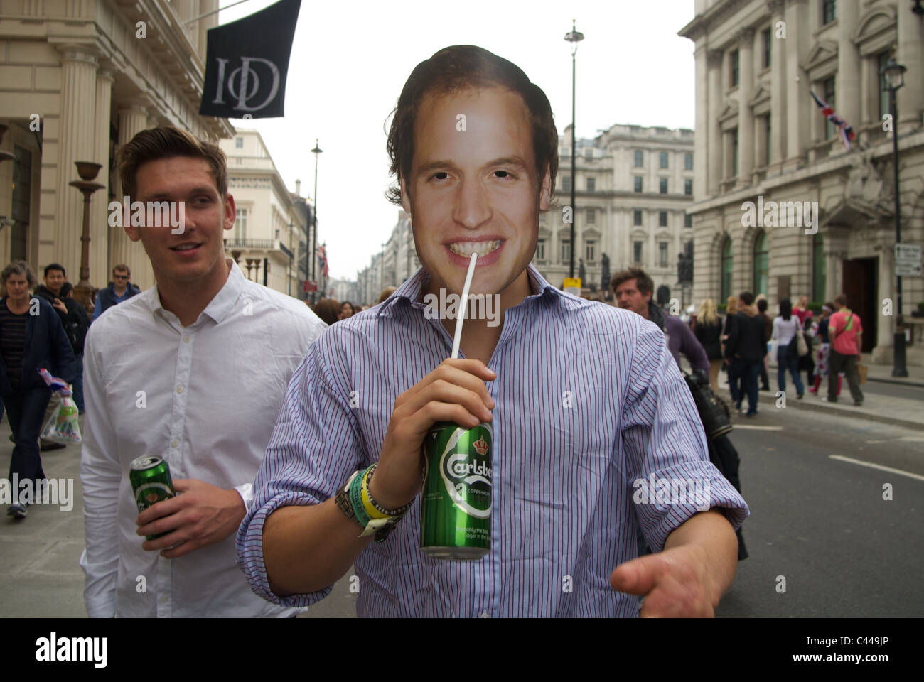 Man wearing Prince William mask and drinking beer through straw while walking along the Mall on Royal Wedding Day. Stock Photo