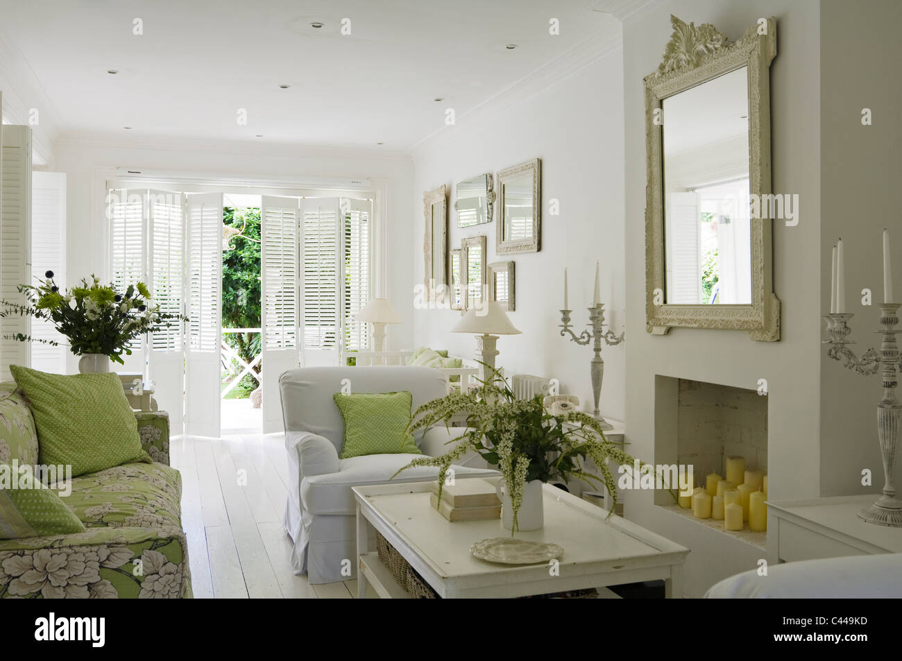 White living room with fireplace, mirror, flower arrangements and ...