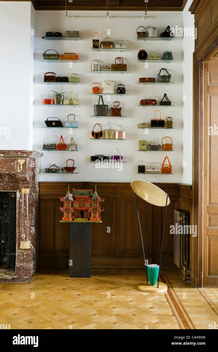 Collection of Lucite handbags displayed on shelving against wall in room with parquet flooring and marble fireplace - Stock Image