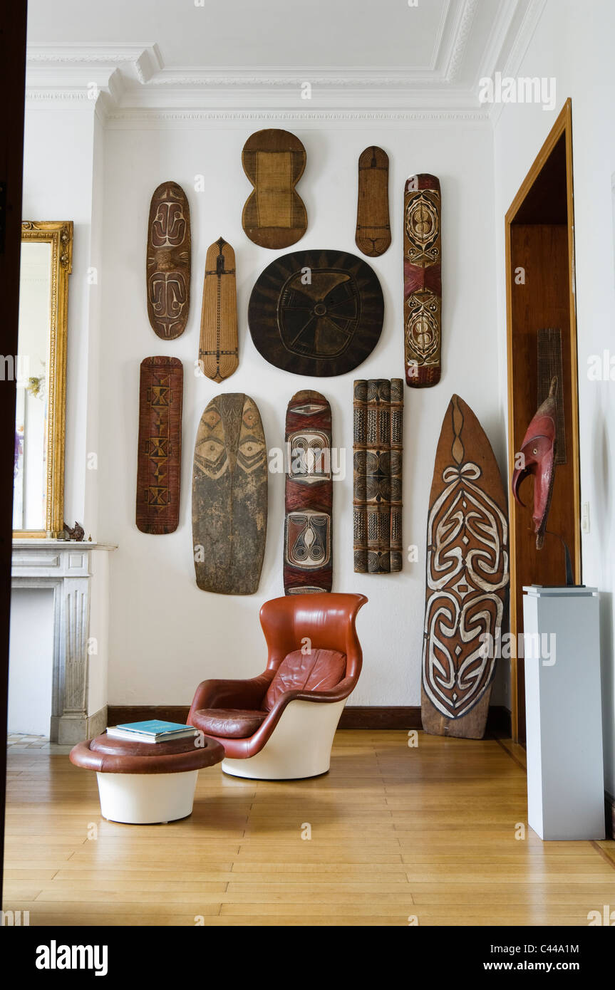 A collection of African tribal shields displayed on a wall in room with oceanic war shield and danish leather chair - Stock Image