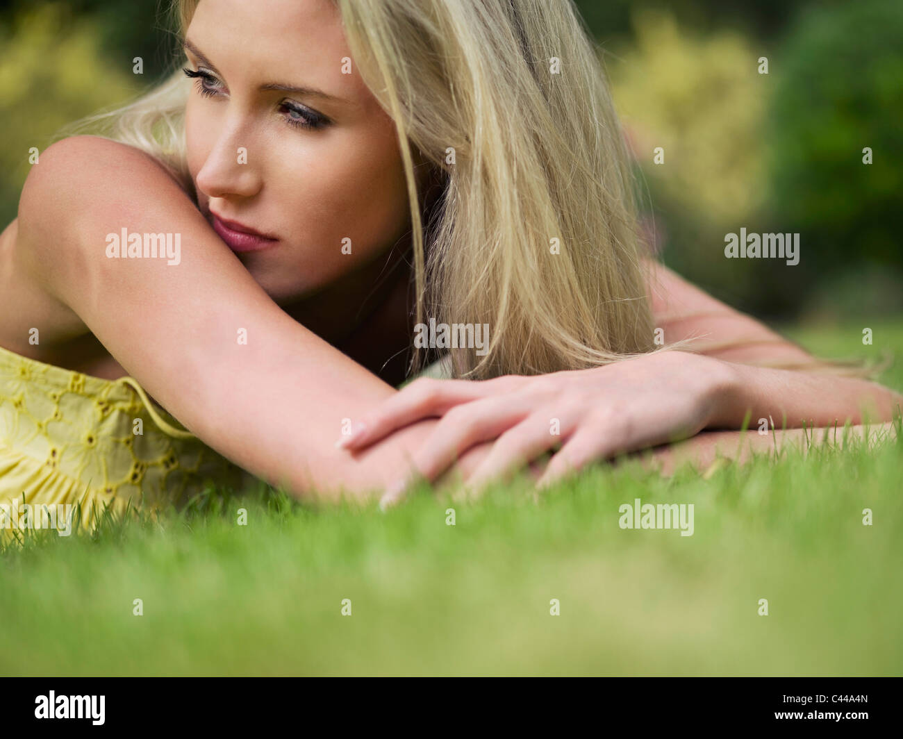 A woman lying in the summer grass, close-up, surface level - Stock Image