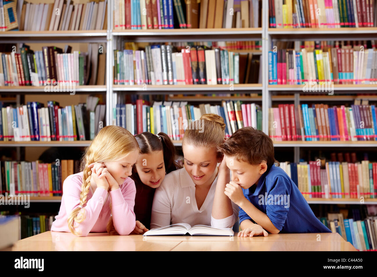 Portrait of pupils and teacher looking at page of interesting book in library - Stock Image