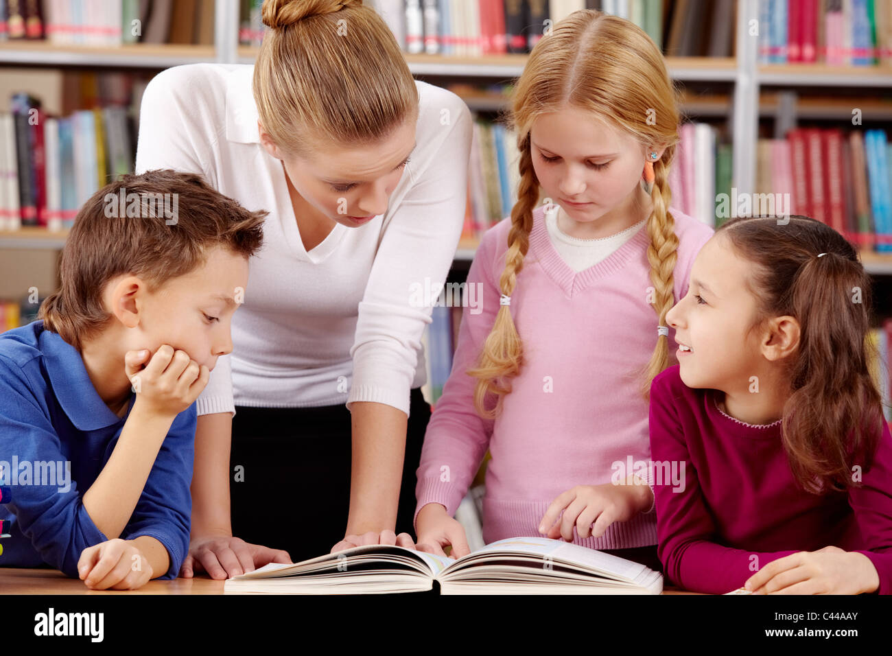 Portrait of pupils and teacher reading and discussing interesting book in library - Stock Image