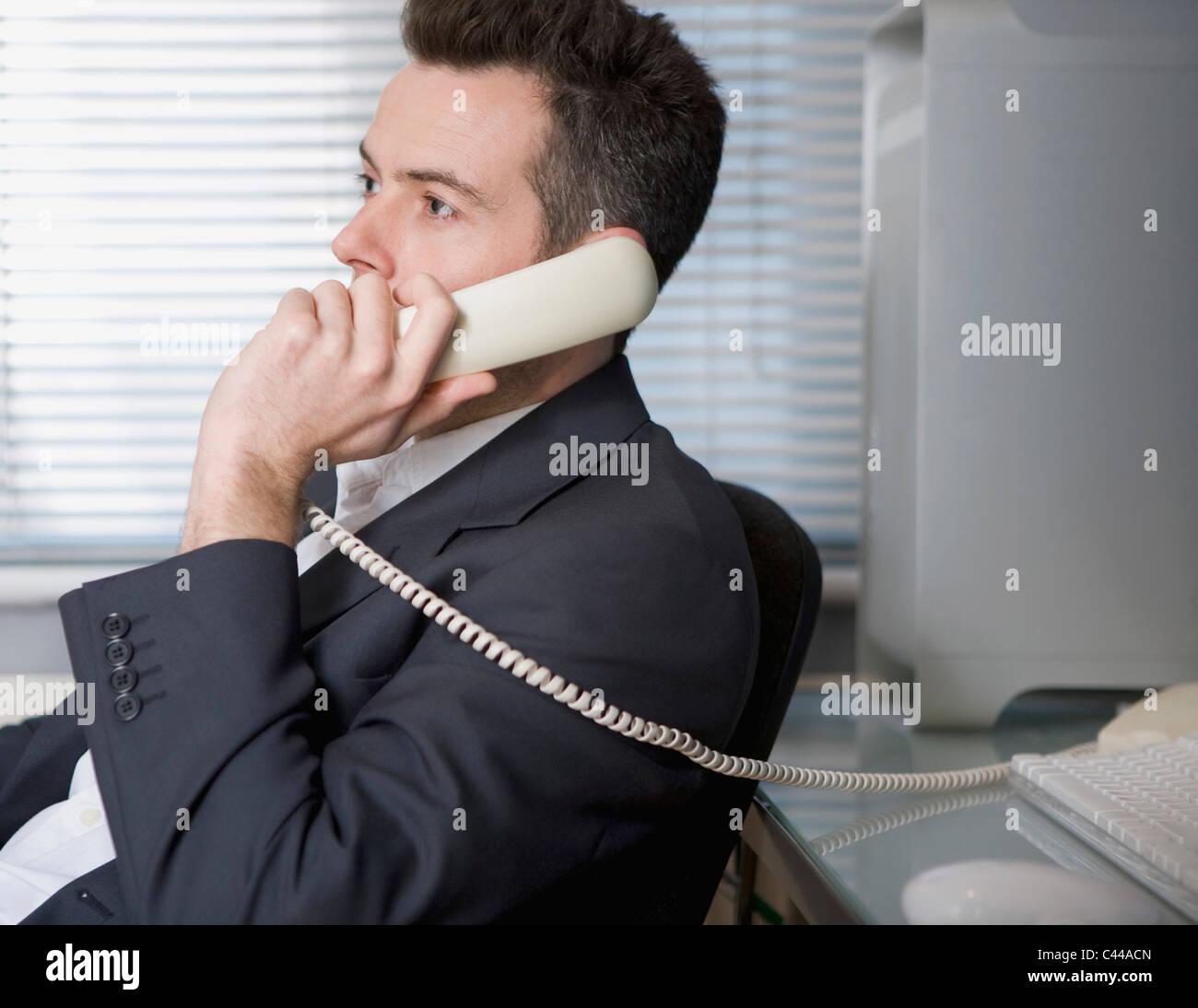 A businessman talking on a landline phone - Stock Image