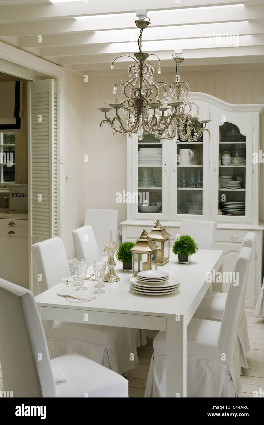 white dining table with chairs, lanterns and chandeliers and cabinet