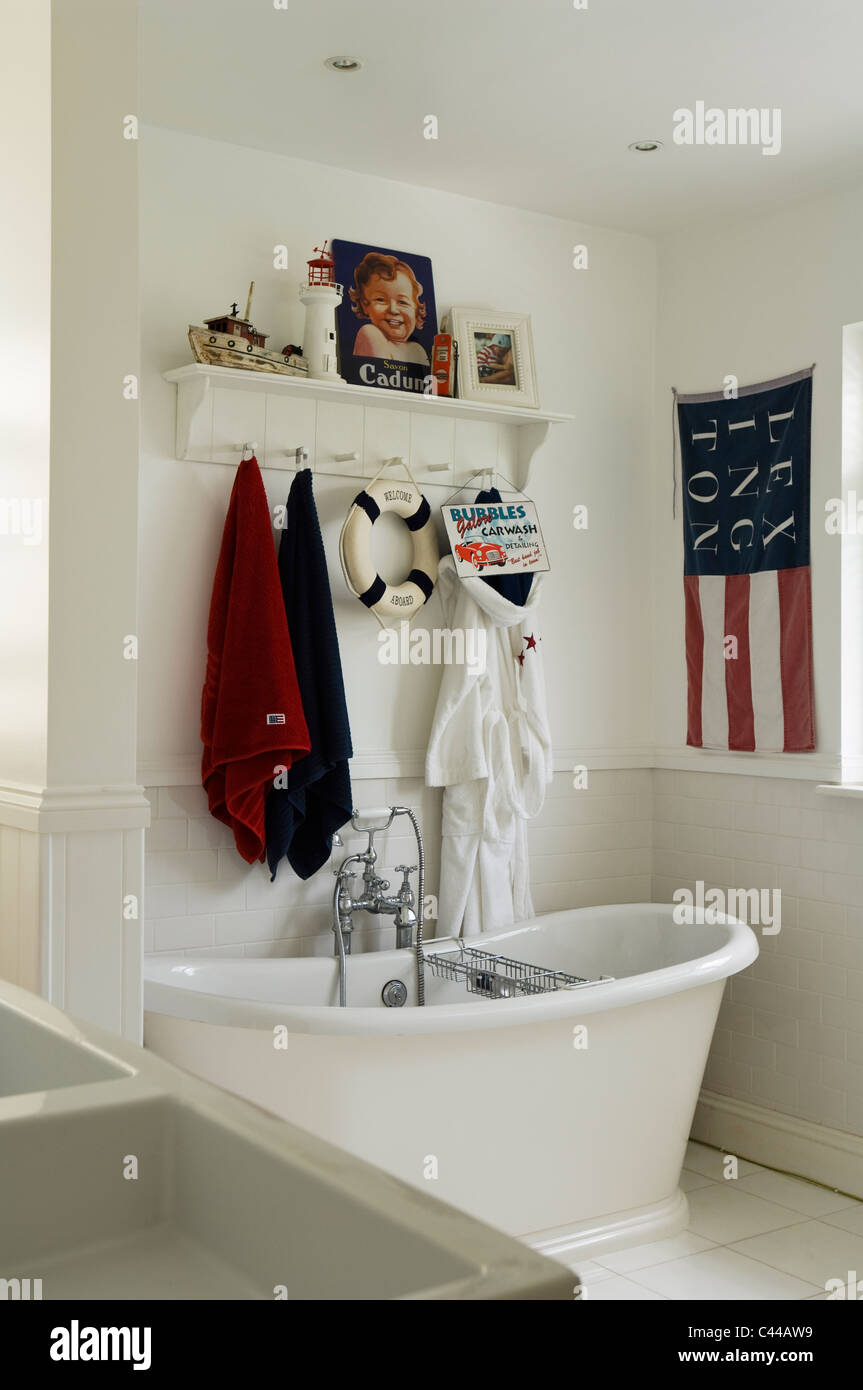 Freestanding roll top bath tub in white bathroom with American style flag and towel rack - Stock Image