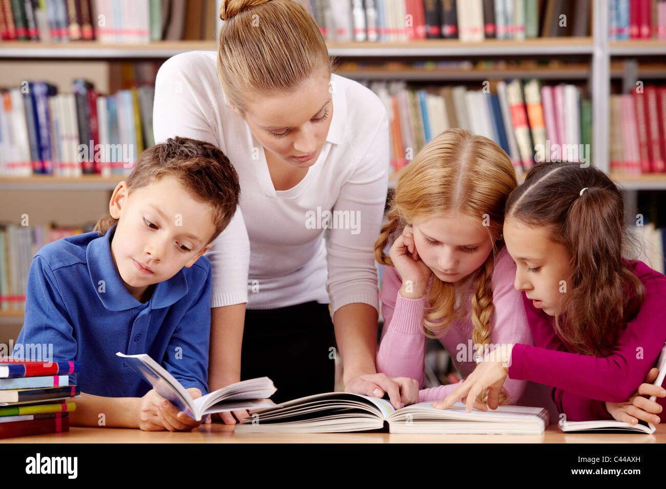 Portrait of pupils and teacher reading interesting book in library - Stock Image
