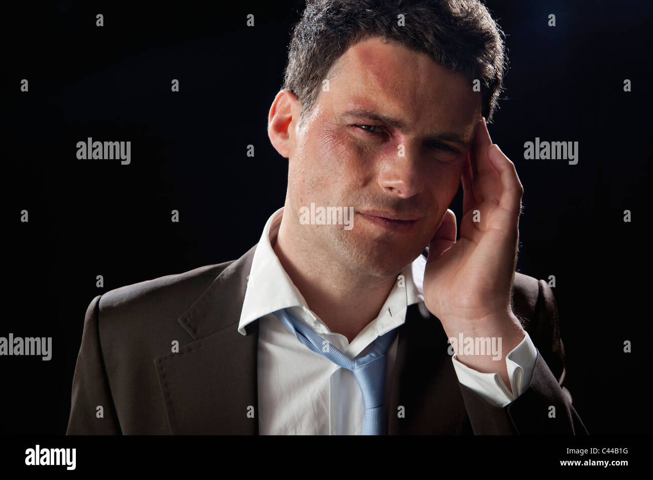 A beaten up businessman wincing in pain - Stock Image