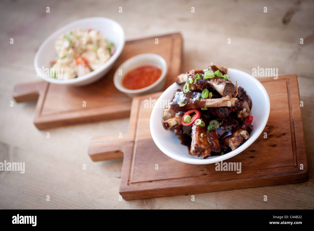 A dish of Chinese sticky pork ribs served with rice noodles and sweet chili dipping sauce, spring onions - Stock Image