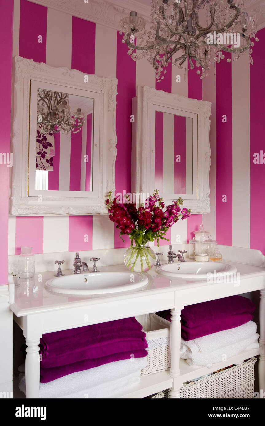 Twin Washbasin Unit With Mirrors In Bathroom With Striped Pink Wallpaper  And Chandelier