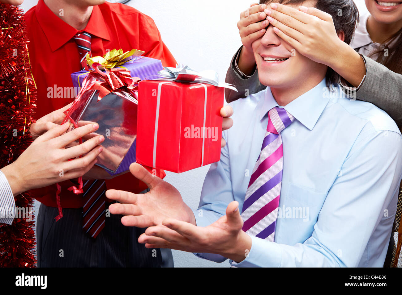 Image of man guessing what present he is going to receive from his colleagues - Stock Image