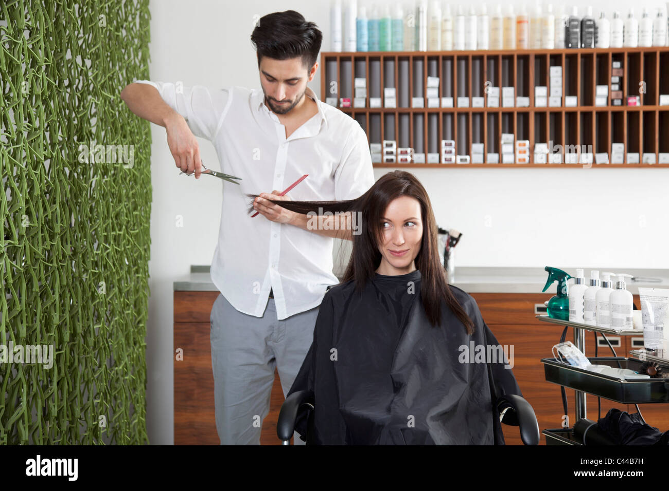 A woman having her hair cut by a male hairdresser - Stock Image