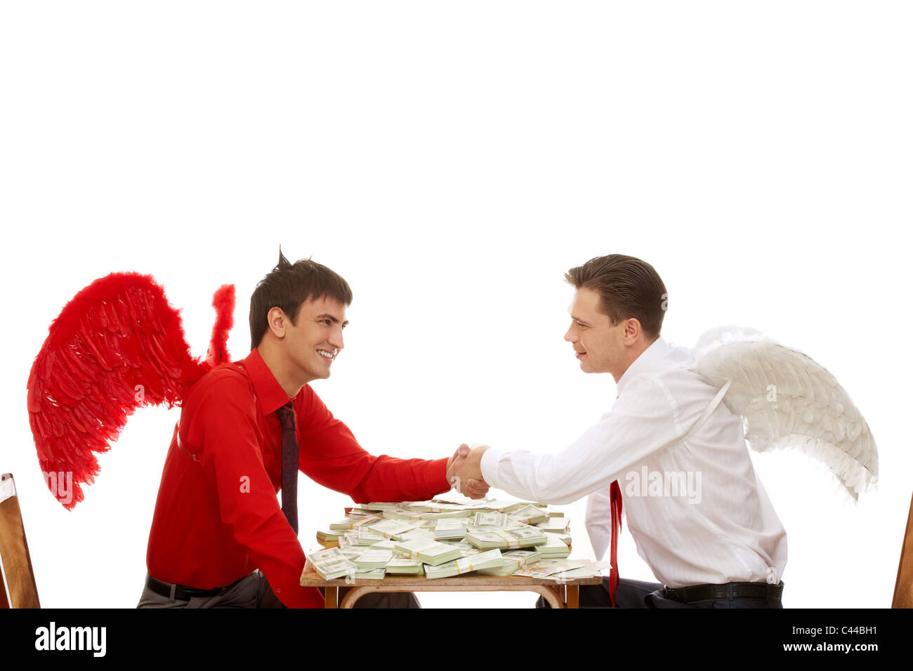 Image of deal between god and devil over table with dollars Stock Photo