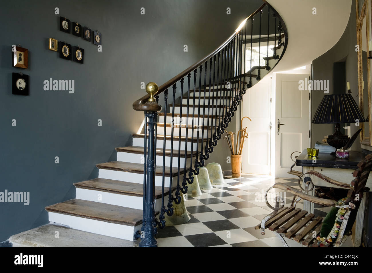 Hallway With Checked Floor Tiles, Oak Wood Staircase With Wrought Iron  Balustrades And Cameos On Wall.