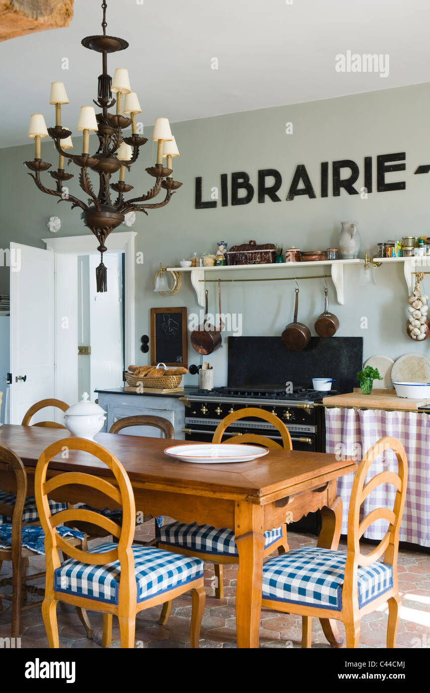 Eclectic kitchen with wooden dining table, lamp chandelier and art deco lettering - Stock Image