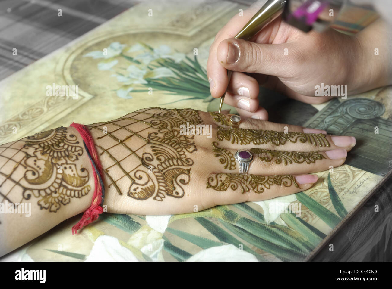 Henna artist applying henna on the hands of the bride's maid. - Stock Image