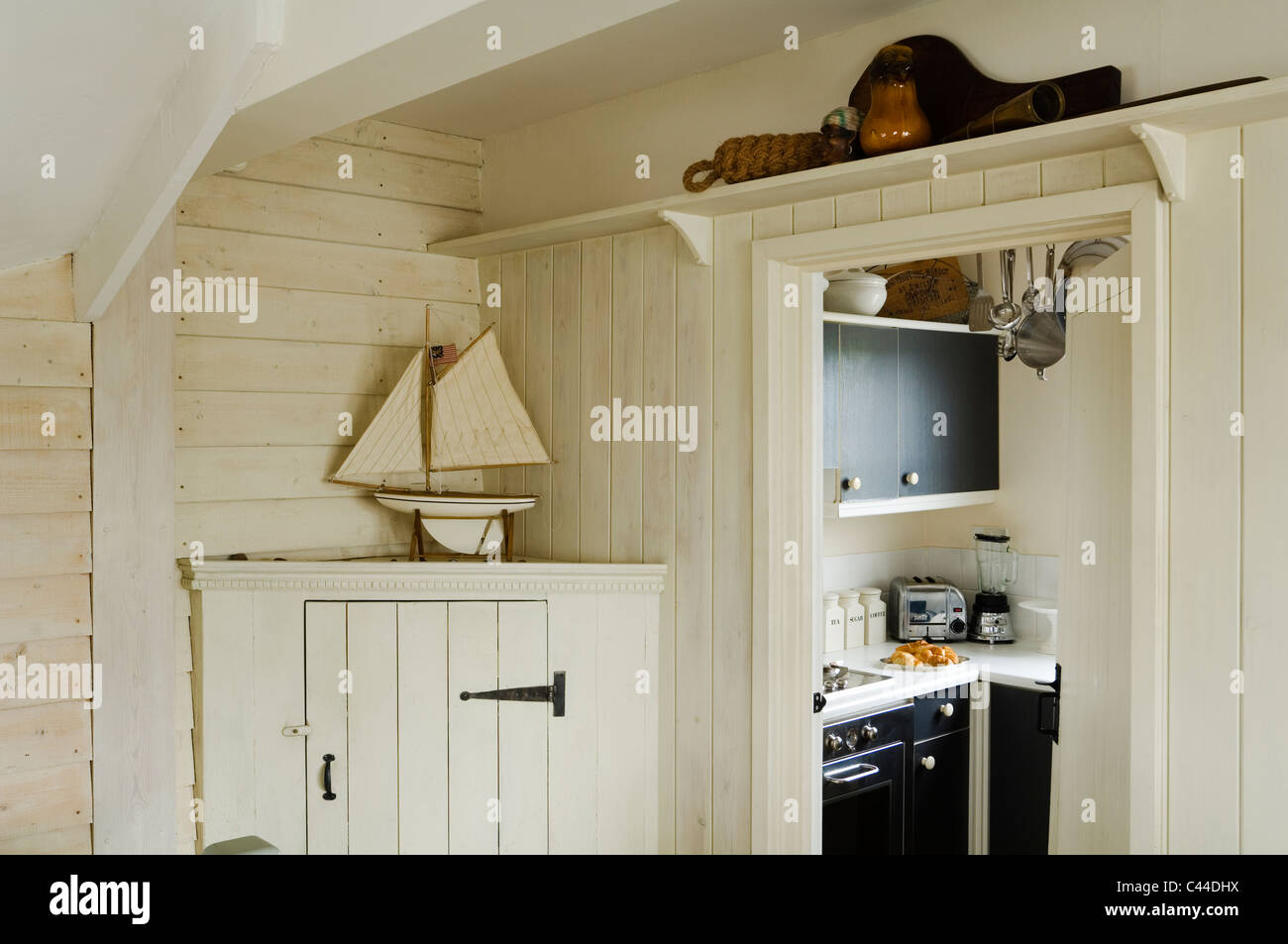 Wood panelled room corner with boat model and view through to kitchen - Stock Image