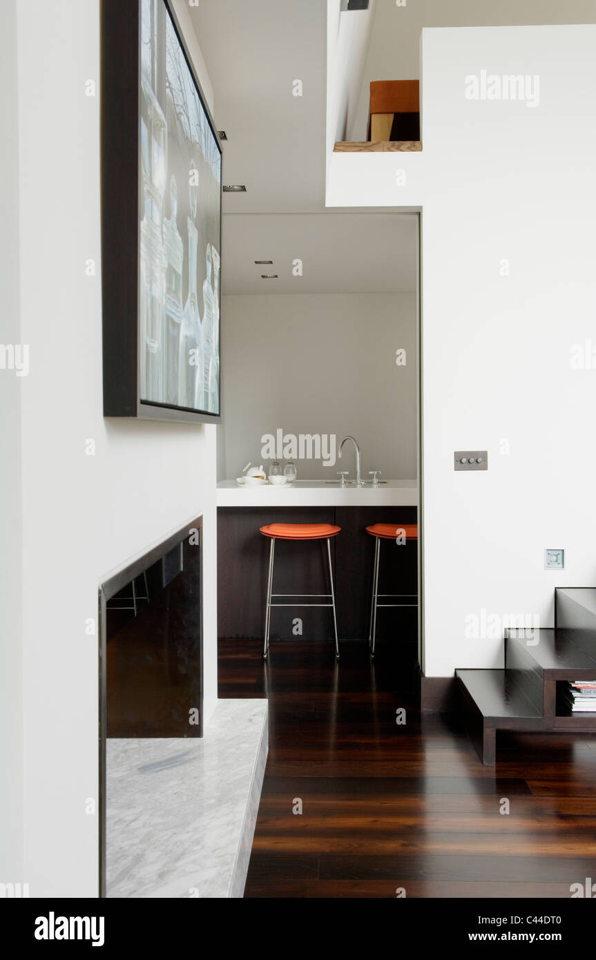 Minimal interior with polished wood flooring, art work, black steps and view through to kitchen bar area - Stock Image