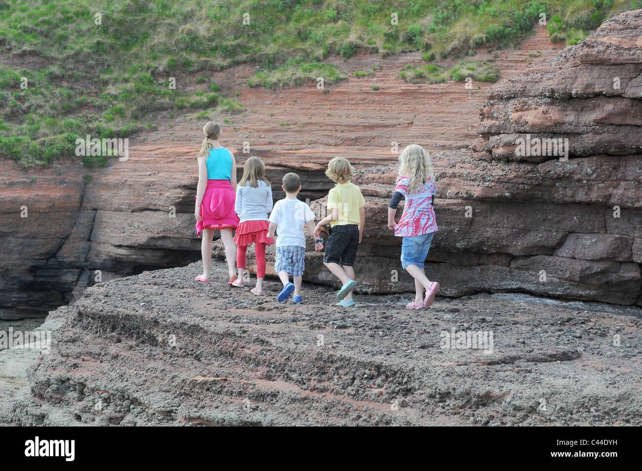 Famous Five Children explore rocks showing coastal erosion in pied piper style,South Devon on the English Riviera - Stock Image