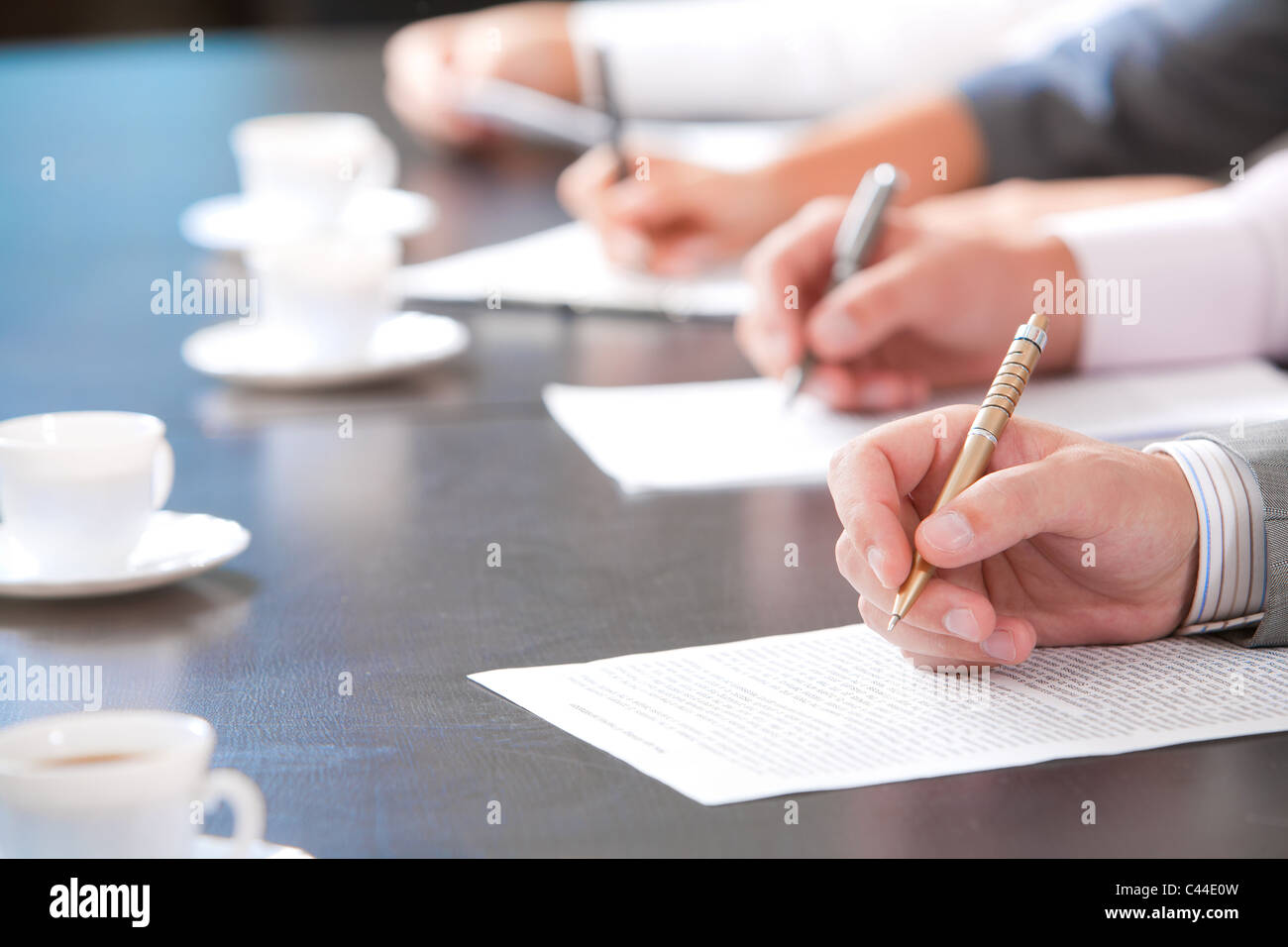 Close-up of masculine hand holding ballpoint over business document on background of human hands with cups of coffee - Stock Image