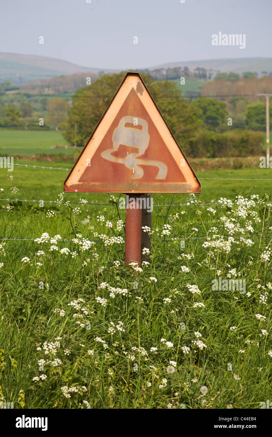 Faded slippery road sign risk of skidding in countryside in Dorset, UK - triangular road sign triangle Stock Photo
