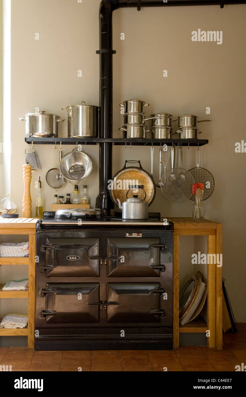 Country style kitchen with aga and saucepans on open shelving Stock Photo