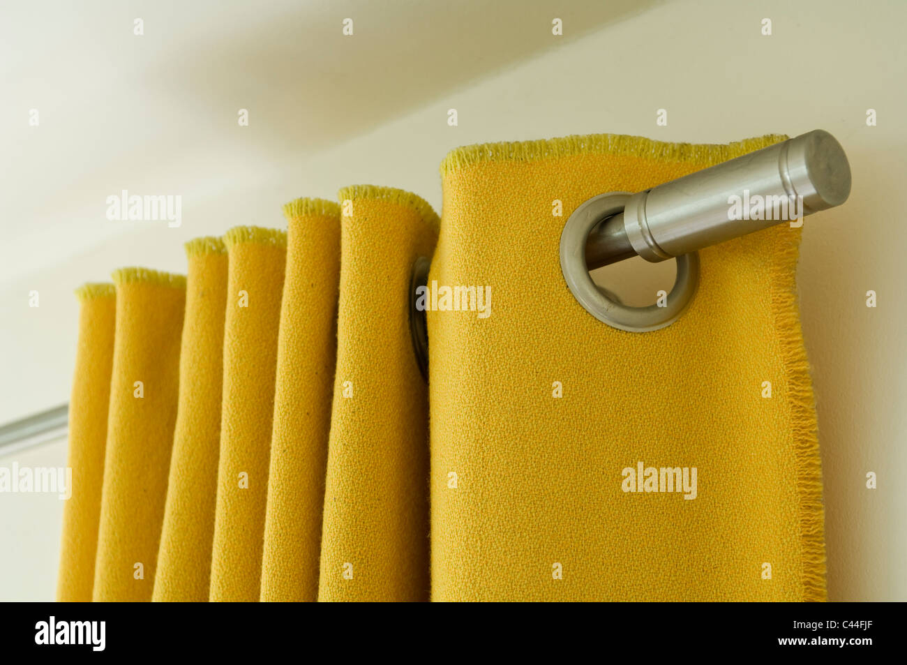 yellow curtain with eyelets hooked on to a stainless steel curtain pole - Stock Image