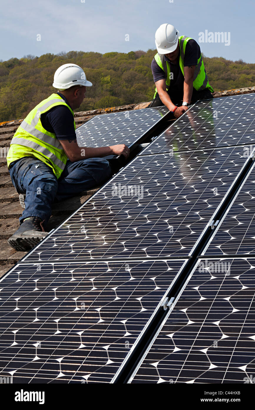 Fitting solar pv photovoltaic panels to house roof Llanfoist Wales UK - Stock Image