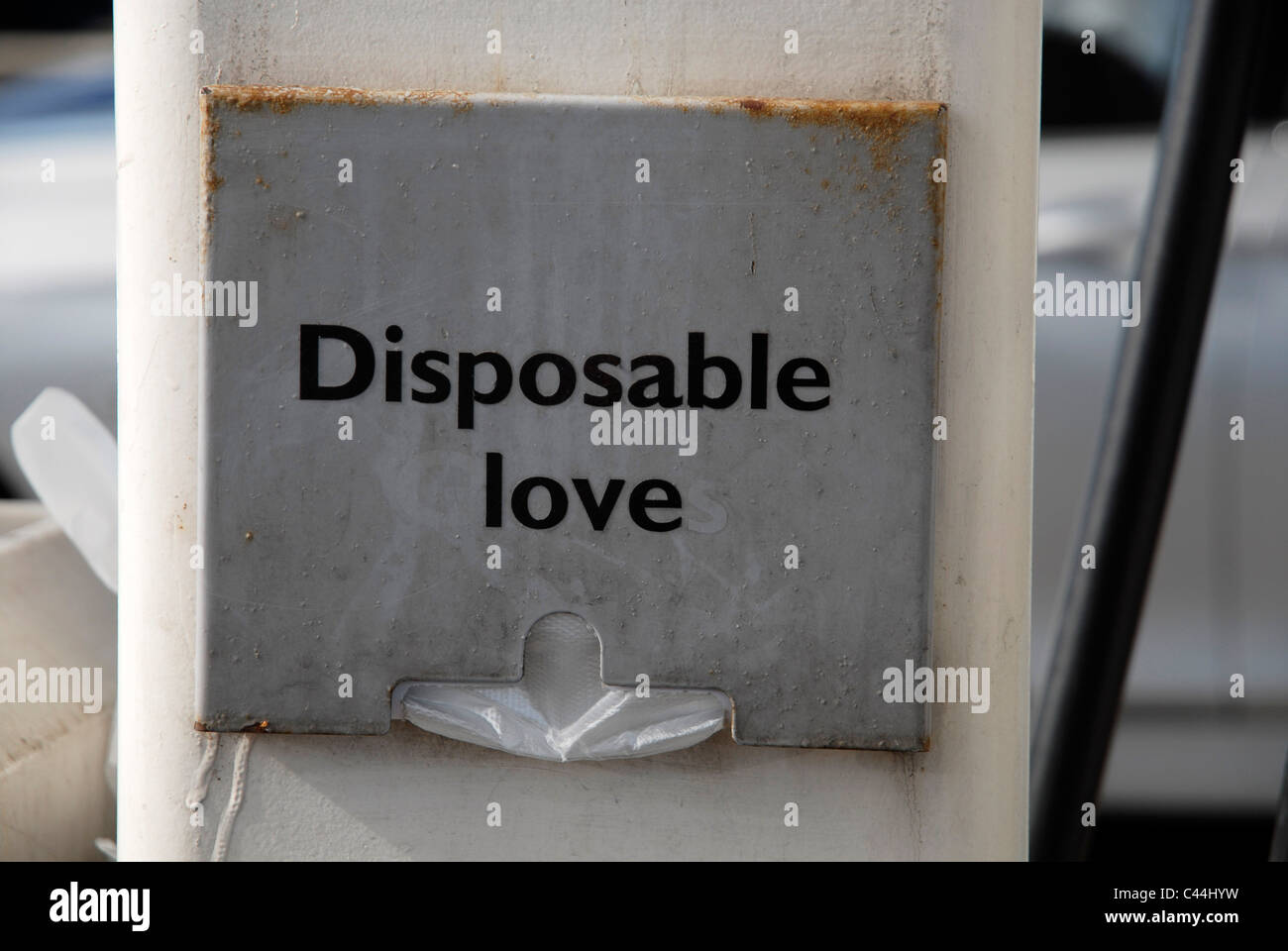 A disposable gloves sign on a diesel pump altered to read 'Disposable love'. - Stock Image