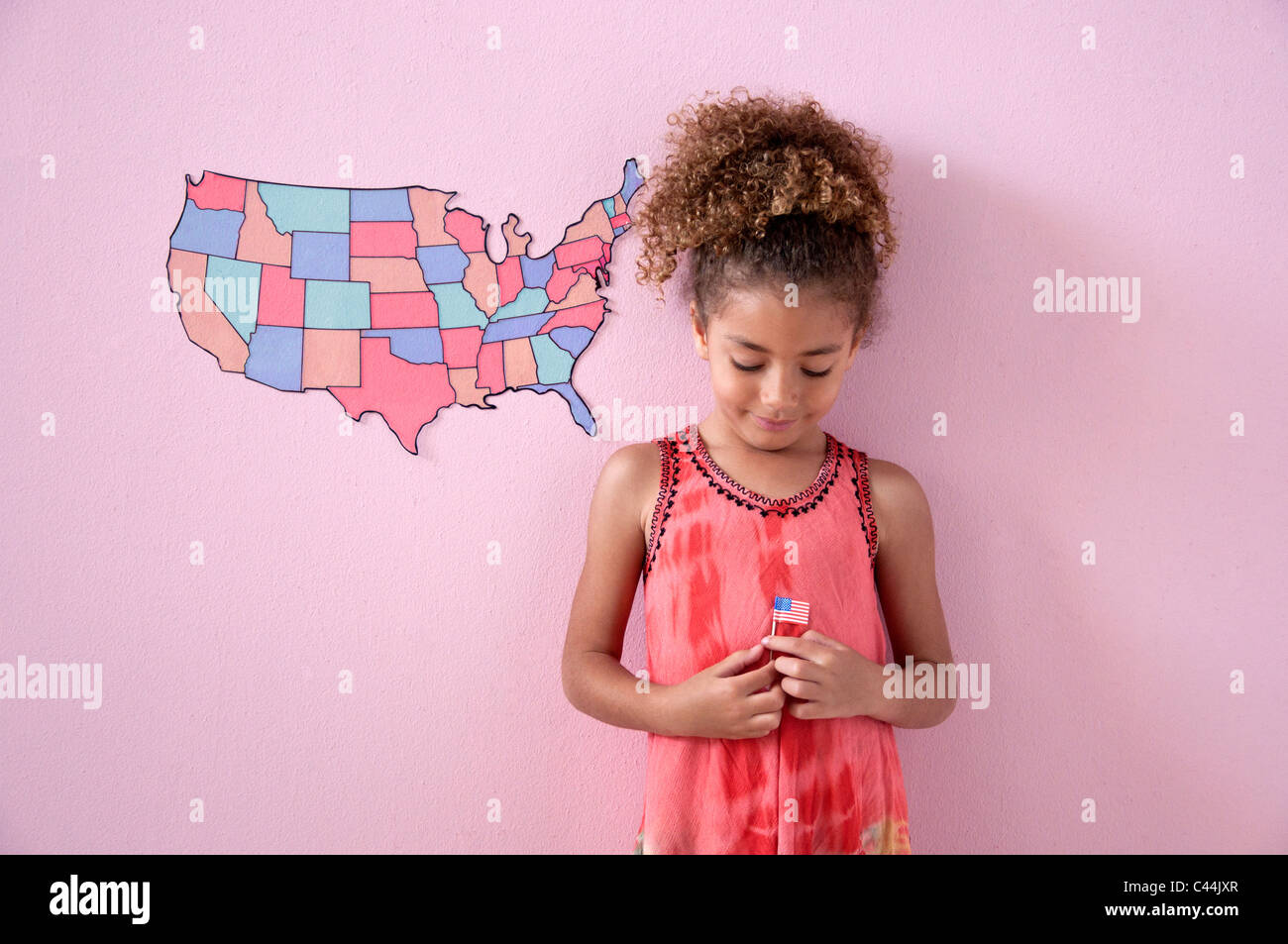 young girl in a pink room with an American map - Stock Image