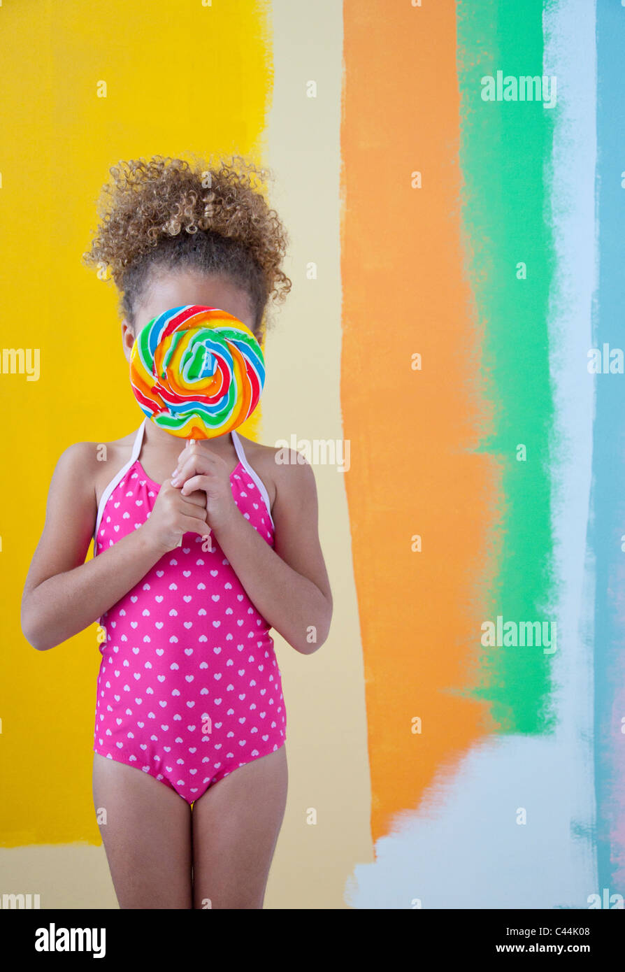 child holding lollipop in front of face - Stock Image