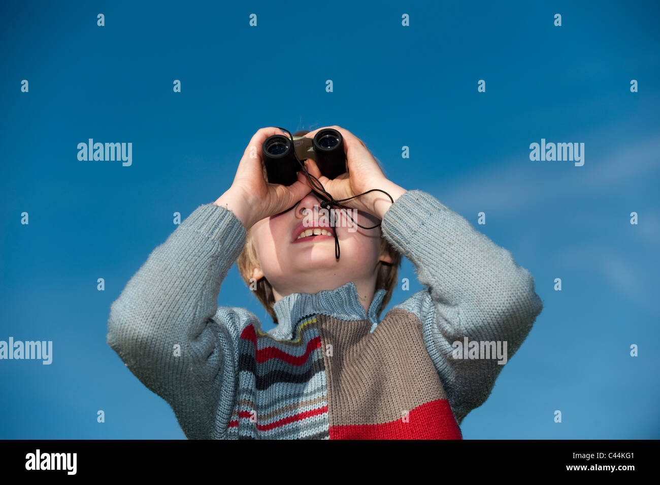 Young boy looking through binoculars - Stock Image
