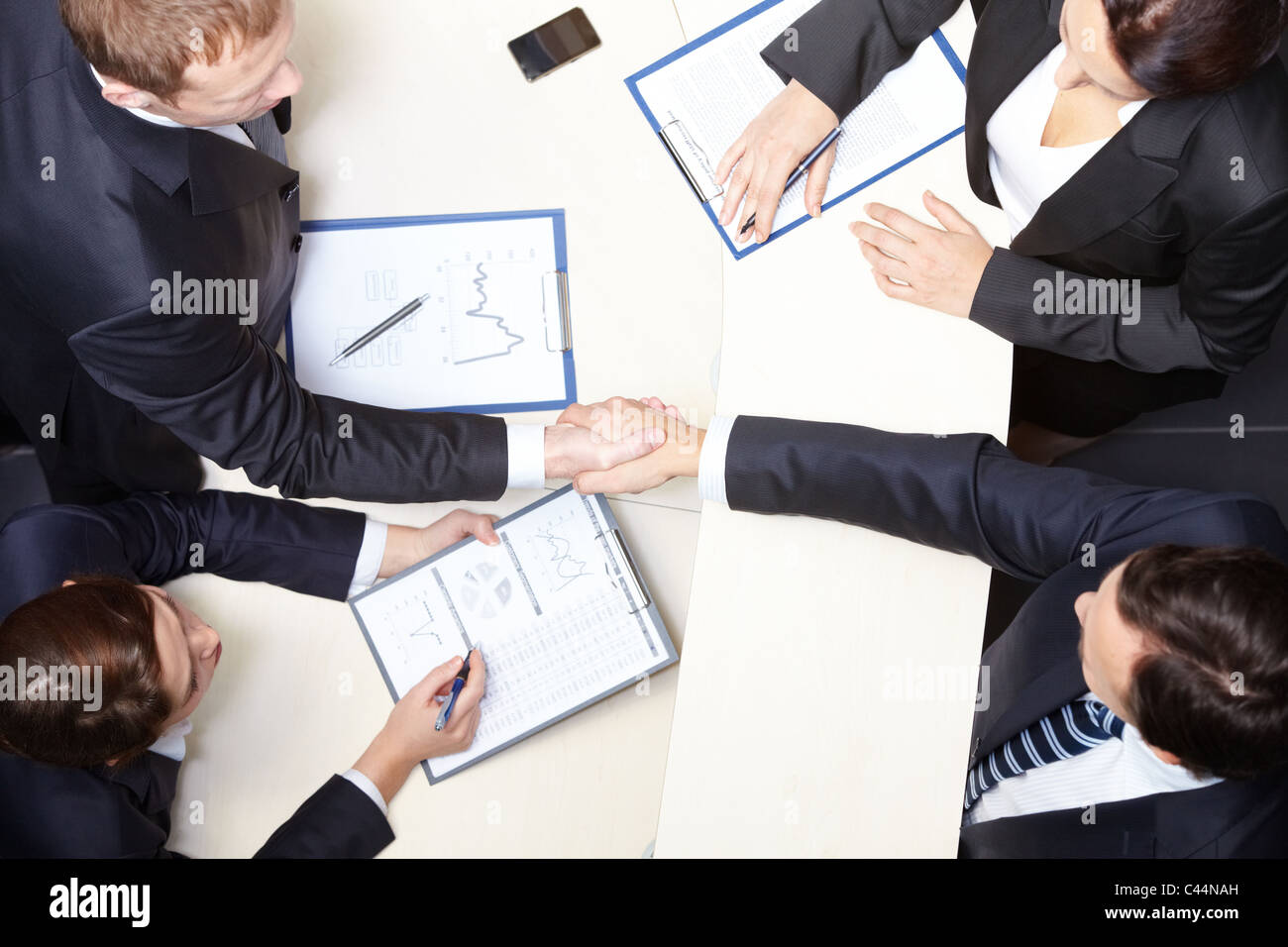 Above view of business partners handshaking after signing contract - Stock Image