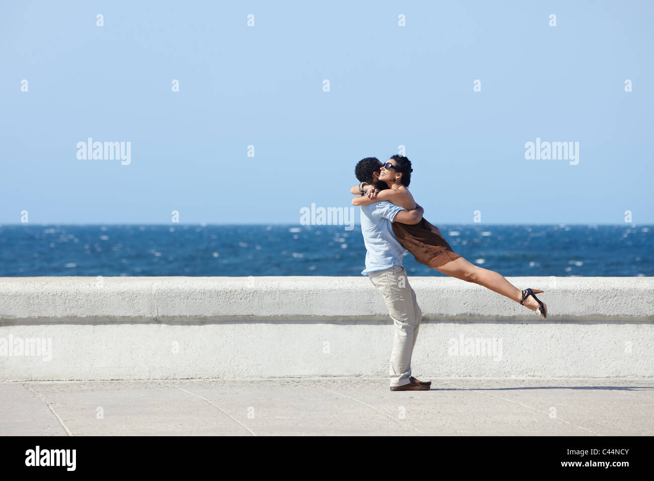 euphoric young couple meeting and hugging near the sea. Horizontal shape, side view, copy space Stock Photo