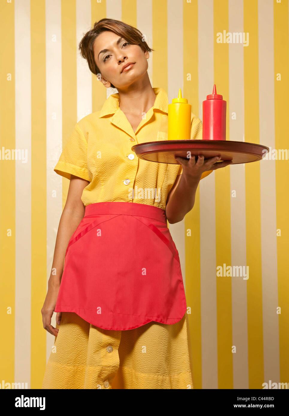 waitress serves ketchup and mustard on tray - Stock Image