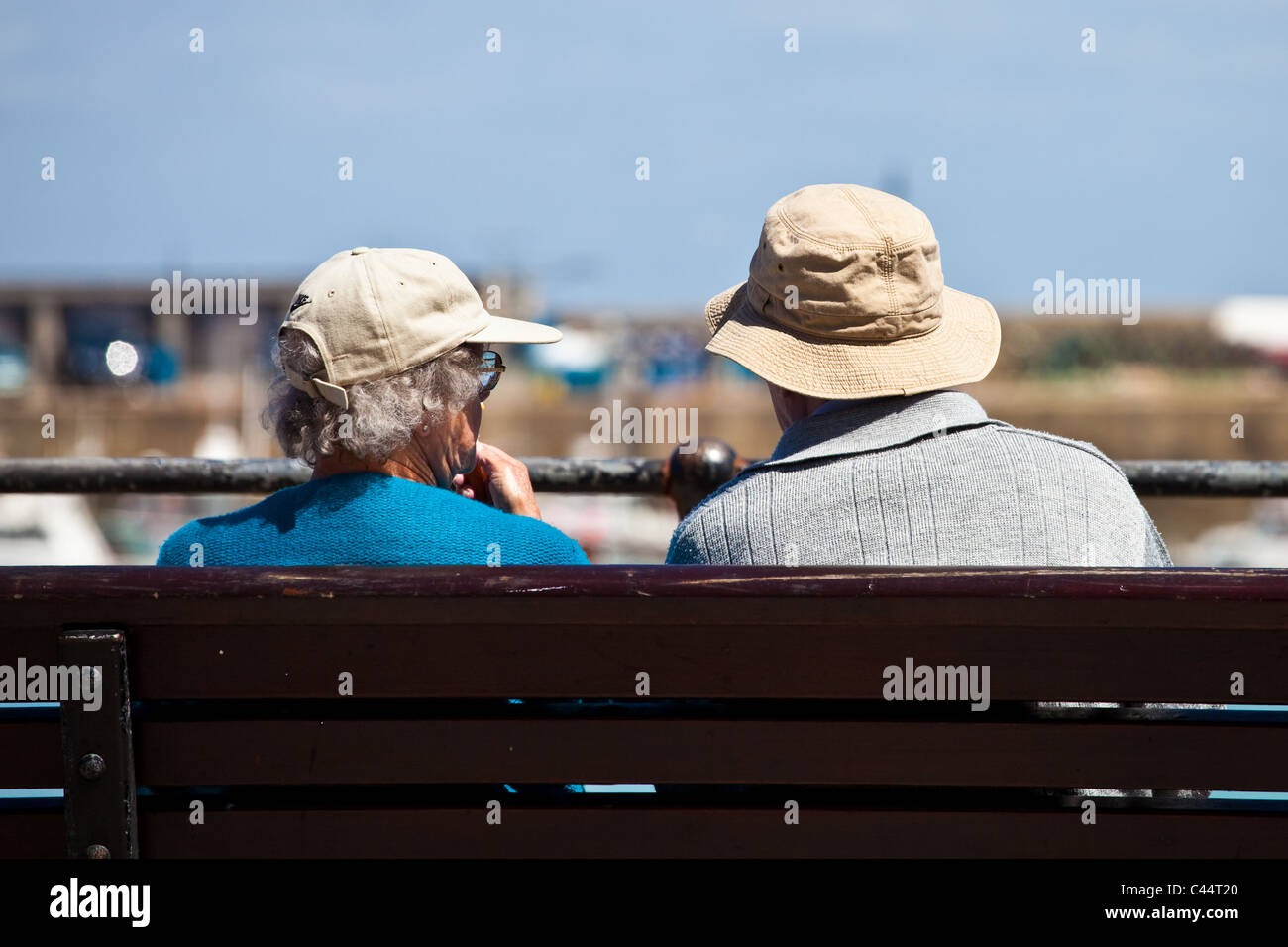 An elderly couple relaxing on a bench in the UK summer - Stock Image