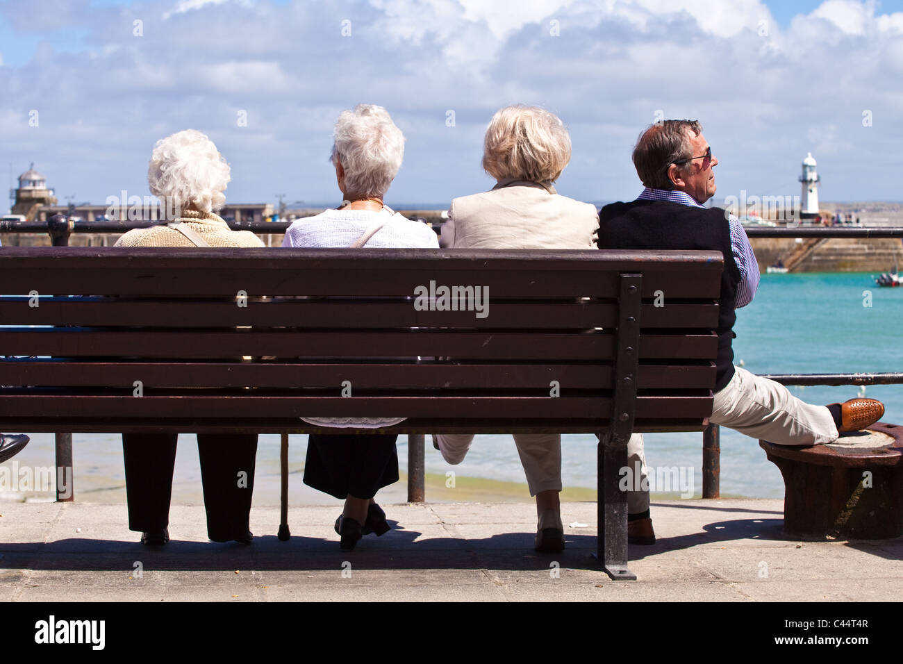 Group of pensioners on a bench at St Ives sea front in UK - Stock Image
