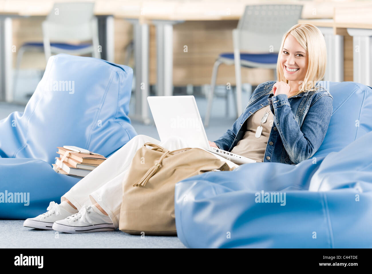 Young happy student girl relaxing at high school with laptop - Stock Image